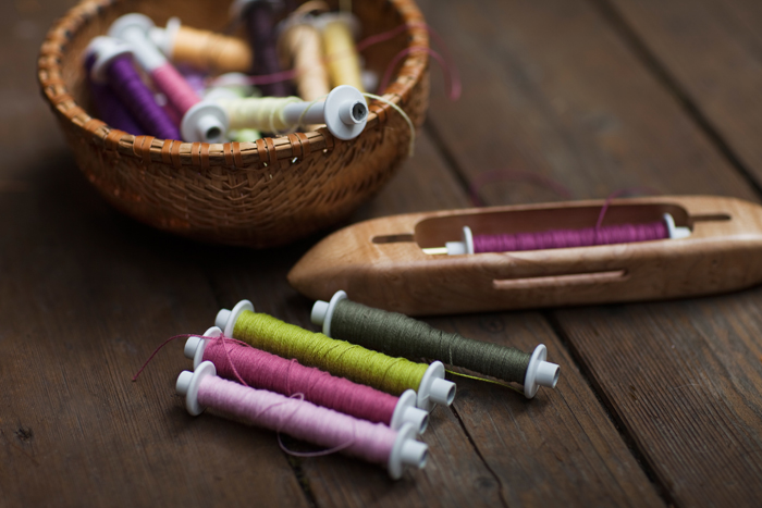 weaving bobbins wound with different colors of cotton