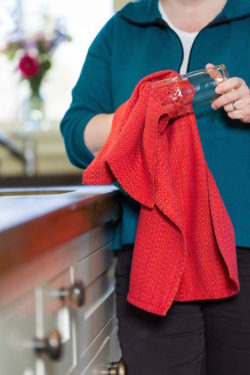 drying a glass with a Sunset kitchen towel