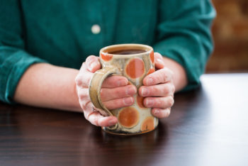 holding a hot cup of tea in a handmade mug