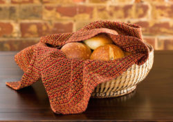 Letting Go kitchen towel in a basket with rolls